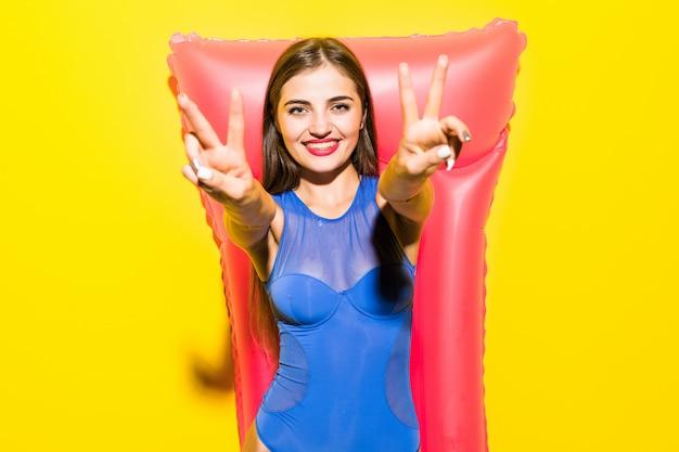 黄色の壁にピンクの膨脹可能なマットレスでポーズビキニの若い魅力的な女性