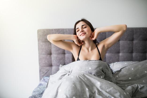 新しい日が始まります。ベッドの上に座っている間髪に手を保つランジェリーの美しい若い女性