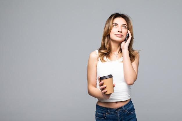 灰色の壁に分離されたコーヒーを飲みながら携帯電話で話しているポーズをとって幸せな若い女の肖像