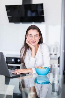 若い女性が台所でラップトップに取り組んでサラダを食べる