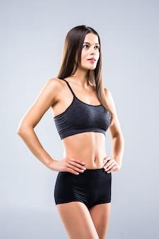 Положение молодой женщины фитнеса изолированное на сером цвете