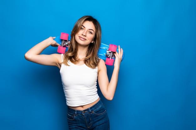 Портрет скейтборда владением красивой молодой женщины над голубой стеной.