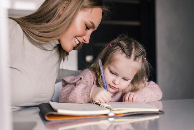 Молодая мать помогает дочери с домашним заданием за столом в столовой