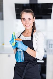 クリーニングのコンセプト。台所でクリーニングツールを保持している若い女性