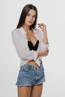 Молодая женщина стоя в студии изолированной на белизне
