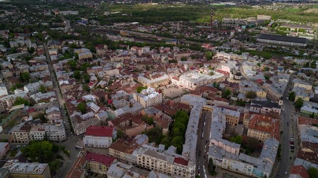 その通り、古い住宅、市庁舎、教会などの美しい古代ウクライナ都市チェルノフツィの中心部の空中夏の景色。美しい町。