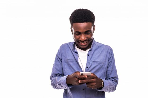Деловой человек текстовых сообщений на своем мобильном телефоне, изолированных на белой стене