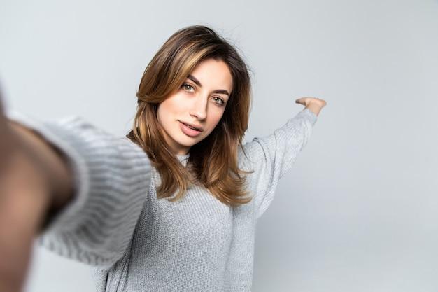 Портрет молодой привлекательной женщины, делая селфи фото на смартфоне, изолированные на серую стену