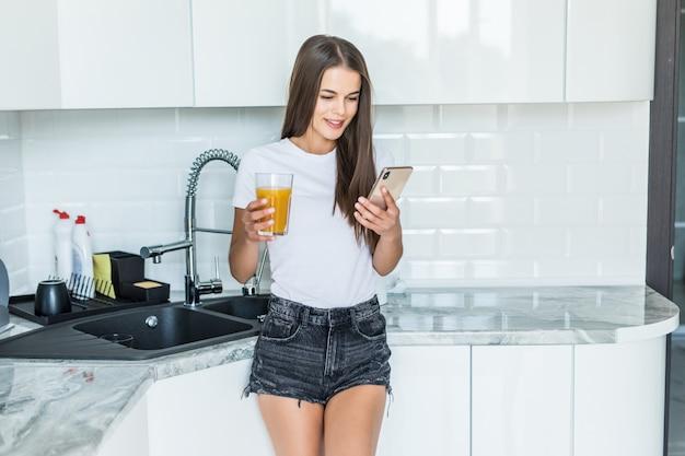 Улыбается женщина, глядя на мобильный телефон и держа стакан апельсинового сока на кухне