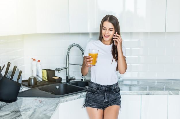 Молодая радостная женщина пьет апельсиновый сок во время разговора по мобильному телефону и стоит возле кухонного стола