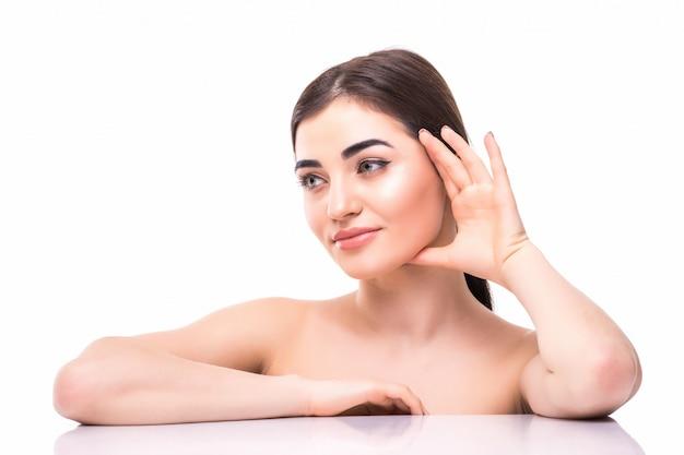 分離された彼女の顔に触れる若い美しい白人女性の肖像画。顔、スキンケア、美容のコンセプトをクリーニング