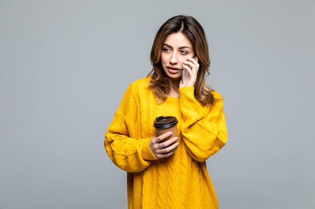 テイクアウトのコーヒーの段ボールカップを持って、灰色の壁に幸せそうに笑って黄色のトップの若い美しい女性の肖像画