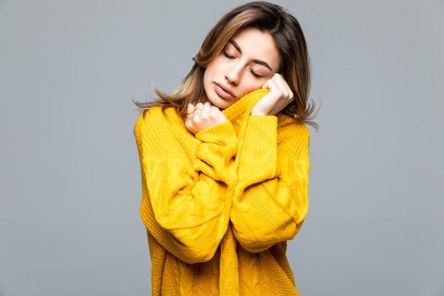 灰色の壁に分離された腕を組んで立っている黄色のカジュアルなセーターの若い美しい女性の交差