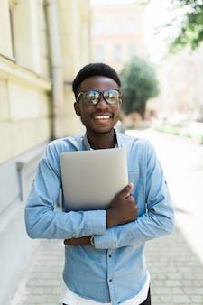 Молодой африканский человек, стоящий на праздновании успеха на улице, глядя на свой ноутбук в руке