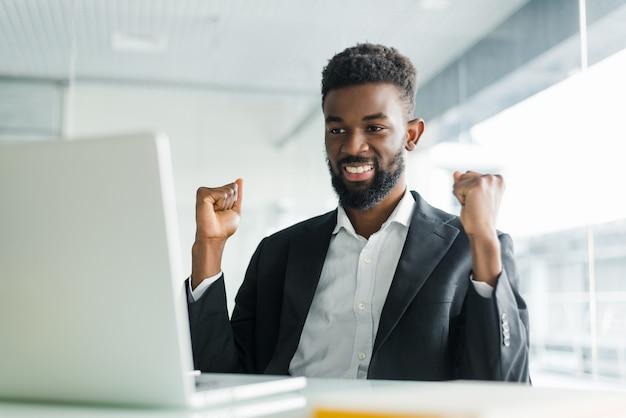 良いニュースをオンラインで興奮してラップトップを見てスーツを着た幸せなアフリカ系アメリカ人のビジネスマン。オフィスの机に座っている黒人の勝者は、ビジネスの成功の結果を祝う手を上げる目標を達成しました