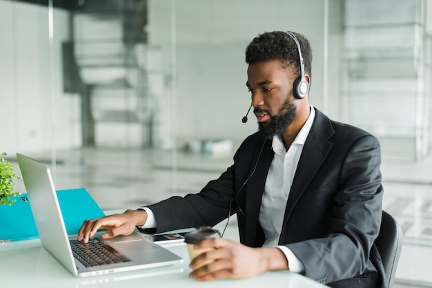 アフリカ系アメリカ人の男性顧客サポートオペレーターがオフィスで働くハンズフリーヘッドセット。
