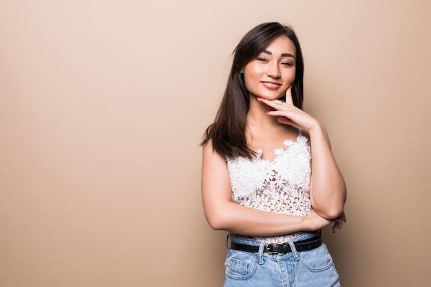 ベージュの壁に分離された美しい若いアジア女性