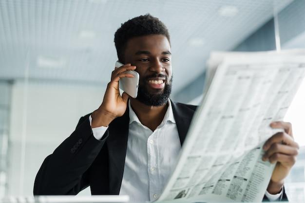 Афро-американский мужчина читает газету и разговаривает по телефону в офисе