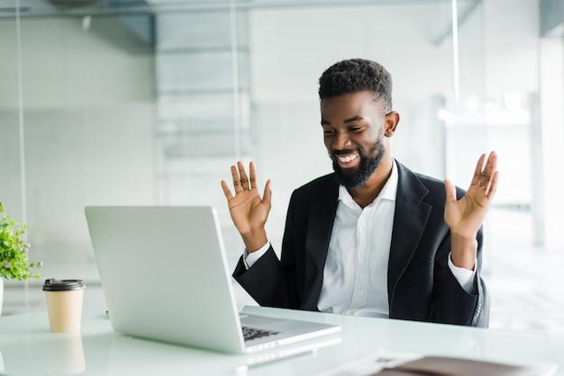 Шокированный афроамериканский бизнесмен в костюме, чувствуя себя ошеломленным новостями онлайн, смотрящими на экран компьютера, сидя на рабочем месте с ноутбуком, подчеркнул инвестор трейдера, удивленный изменениями на фондовом рынке