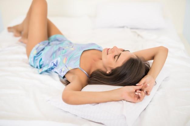 Портрет красивой молодой женщины, лежа на кровати с ногами на кровати в спальне