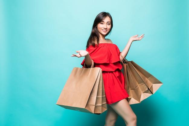 Счастливая женщина покупок азиатских холдинг сумки, изолированных на зеленой стене.