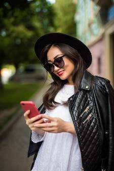 Сотовый телефон молодой азиатской женщины отправляя смс в улице города