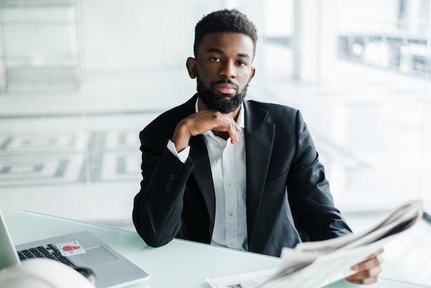 ビジネスセンターオフィス近くの新聞でハンサムなアフリカ系アメリカ人実業家