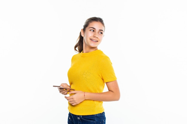 Молодая девушка пользуется мобильным телефоном, изолированным на белой стене