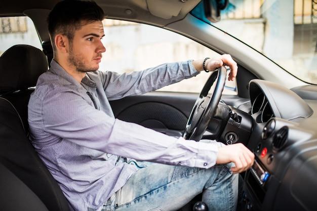 輸送、出張、技術、人々の概念。車を運転してコントロールパネルのステレオシステムで音楽の音量を調整するスーツを着た若い男