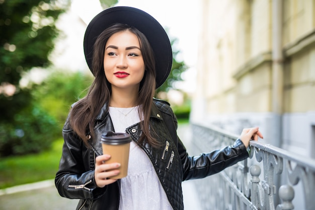 Молодая красивая азиатская девушка с бумажным стаканчиком кофе гуляя по городу лета