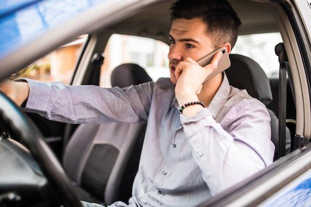 車を運転して携帯電話で話す若いハンサムな男の肖像画。