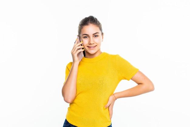 Молодая счастливая девушка звонит с мобильным телефоном на белом