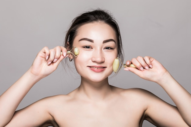 Красивая молодая азиатская женщина используя нефритовый ролик стороны на ее безупречной коже. красота лица крупным планом. концептуальные процедуры для лица с полудрагоценными камнями. изолированные на сером с копией пространства