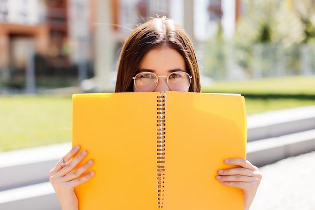 屋外のノートブックで彼女の顔を覆っている若い女性
