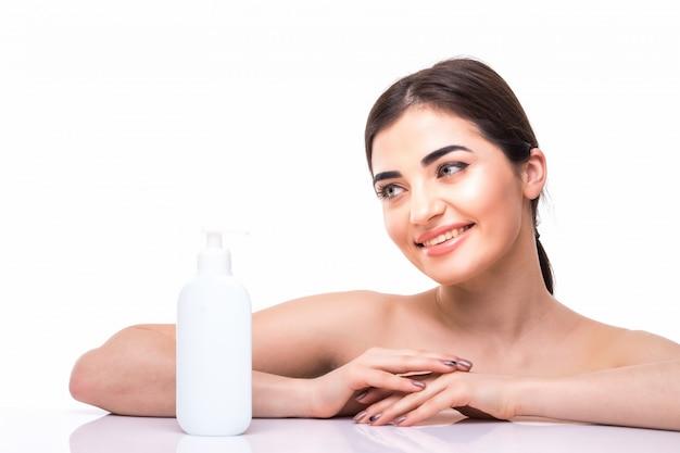 Концепция красоты. кавказская красотка с идеальной кожей, держа бутылку масла. концепция ухода за кожей и косметология