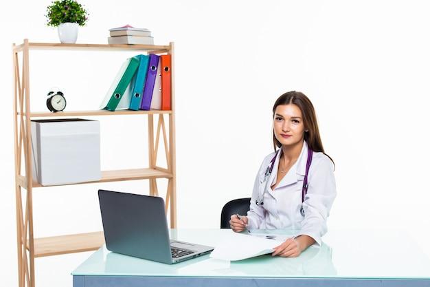 白い壁に分離された笑みを浮かべてレポートを作る医師のオフィスに座っているラップトップを持つ医師