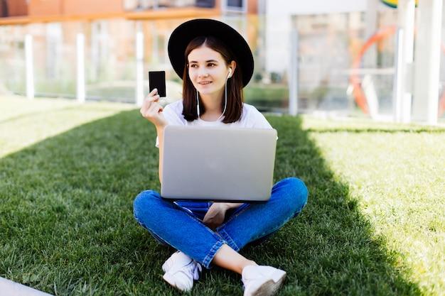 Молодая милая одежда женщины держа кредитную карточку и используя компьтер-книжку для покупки пока сидящ на зеленой траве в парке