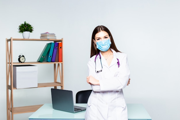 オフィスで聴診器を保持している彼女の胸に交差させた手で立っている女性医学療法士医師の肖像画。医療支援または保険の概念。