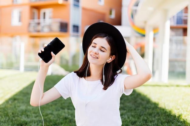 都市の幸せな女が通りを歩いています。かわいい女の子は、ヘッドフォンで音楽を聴いたり、通りで踊ったり、笑ったりしています。