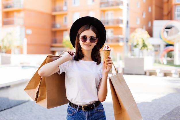 Привлекательная девушка гуляет с мороженым, держа сумки в торговом центре