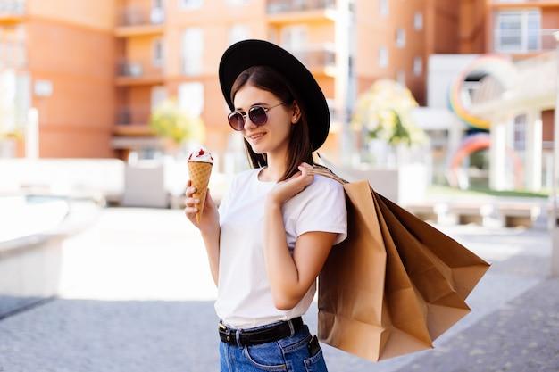 ショッピングモールで買い物袋を保持しているアイスクリームと一緒に歩いている魅力的な女の子
