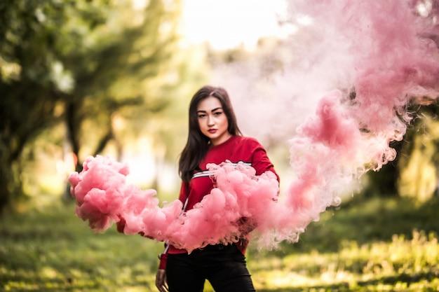 屋外の公園で赤いカラフルな煙爆弾を保持している若いアジア女性。お祝いまつりで広がる赤い煙。