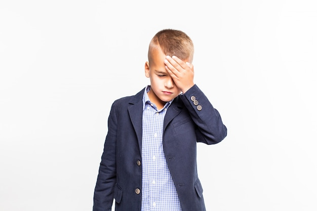 Грустный мальчик, держа голову, изолированные на белой стене