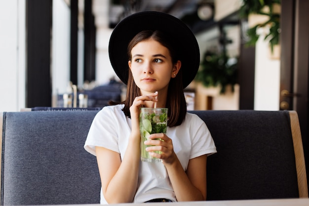 美しい若い女性がカフェでレモネードを飲む