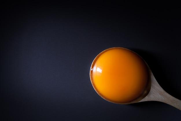 コピー用のスペースと黒の背景に木のスプーンで卵黄