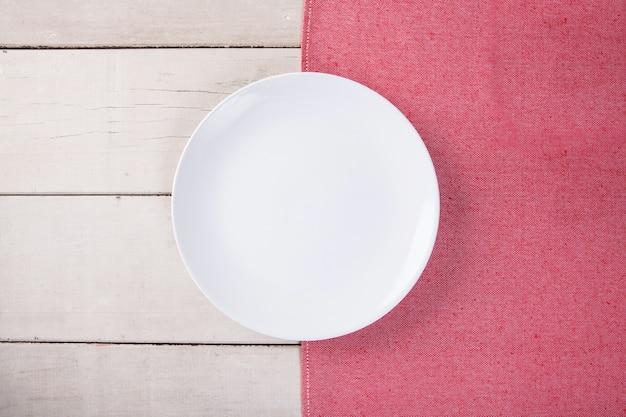 赤いテーブルクロスと白い木のテーブルにコピーのためのスペースを置いて空の白いプレートのトップビュー。