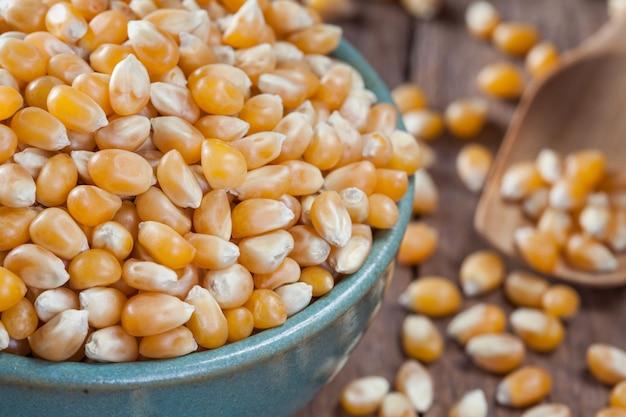 Сухие зерна кукурузы в зеленой миске, на деревянном столе.