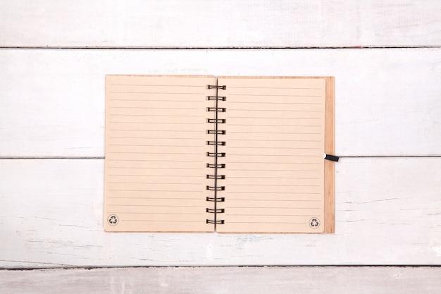 木製テーブル上のノートブック再生紙の空白。