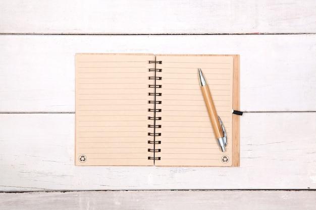 ノートリサイクル紙の上にペンが付いている木製のテーブルに空白。