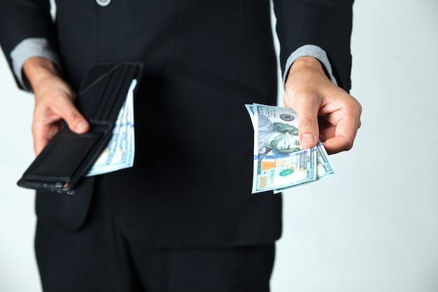 その実業家は、支払いや寄付のために彼の財布からドルを取り出した。